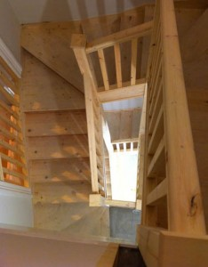 Carpentry service showing bespoke installed staircase made of pine, split over two levels with square posts and ballustrades