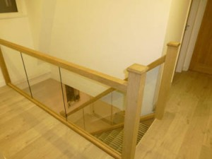 Carpentry service of a bespoke staircase made from light oak, with a glass fitting balustrade and laquer finish